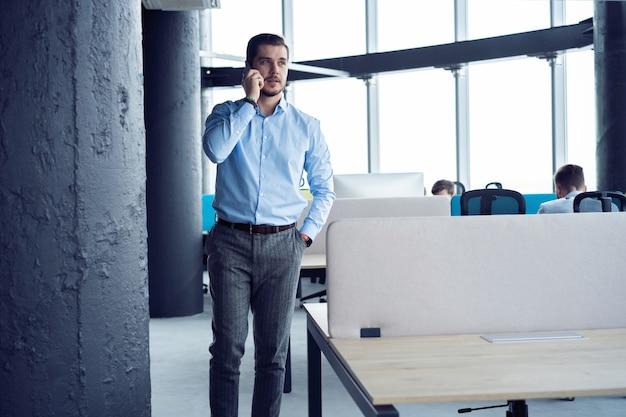 Homem de negócios maduros em pé dentro de um prédio de escritórios e usando o telefone celular.