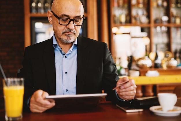 Homem de negócios maduros está navegando na internet e segurando um cartão de crédito na mão.