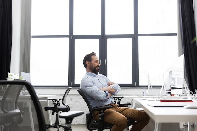 Homem de negócios maduros, sentado em uma cadeira com os braços cruzados