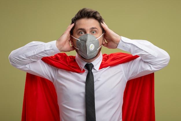 Homem de negócios maluco de super-herói com máscara facial protetora e capa vermelha com um olhar maluco de surpresa, de mãos dadas na cabeça em pé sobre a parede verde