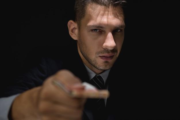 Homem de negócios manhoso dando dinheiro de suborno em sombra escura