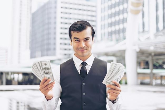 Homem de negócios, mantendo o dinheiro nos notas de dólar no conceito urbano de distrito de negócios para o negócio de sucesso
