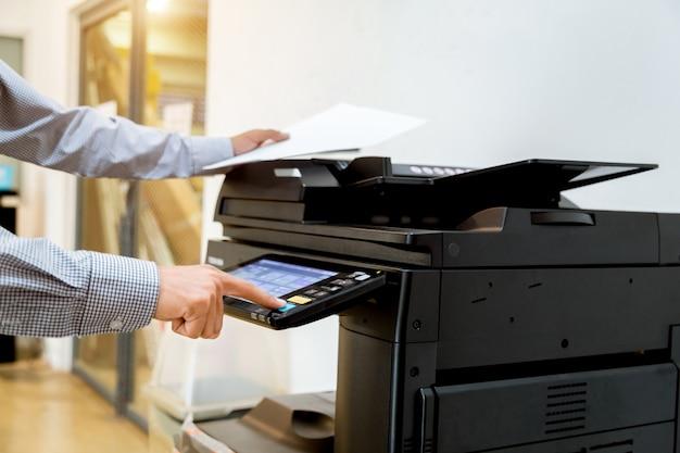 Homem de negócios mão pressione o botão no painel da impressora, impressora scanner de laser de escritório máquina de cópia suprimentos começar