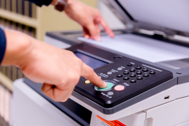 Homem de negócios mão pressione o botão no painel da impressora.