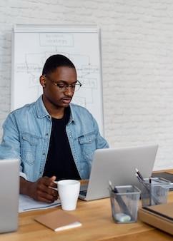 Homem de negócios médio trabalhando em um laptop