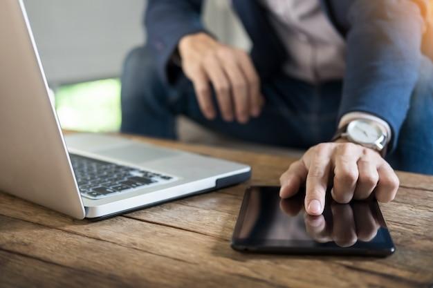 Homem de negócios moderno com notícias de leitura de computador em computador na manhã no café