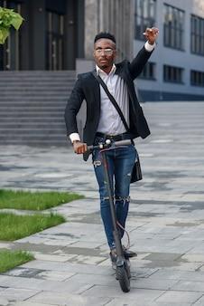 Homem de negócios moderno de pele escura anda de scooter elétrico após terminar seu dia de trabalho no escritório.