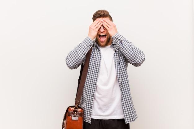 Homem de negócios moderno jovem cobre os olhos com as mãos, sorri amplamente esperando por uma surpresa.
