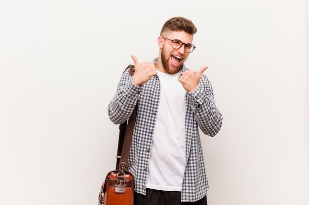 Homem de negócios moderno jovem levantando os dois polegares para cima, sorrindo e confiante.