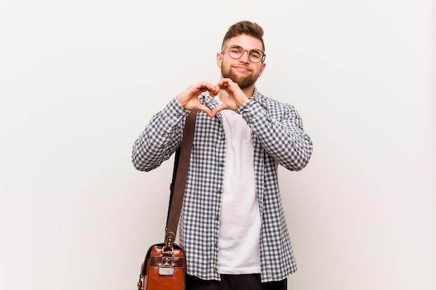 Homem de negócios moderno jovem sorrindo e mostrando uma forma de coração com as mãos