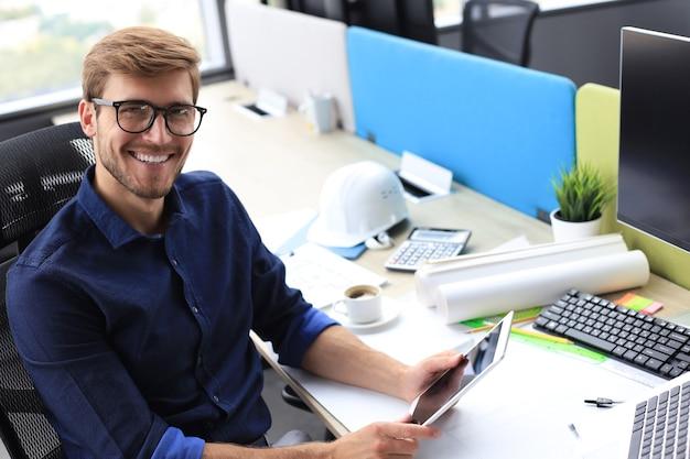 Homem de negócios moderno jovem trabalhando usando tablet digital enquanto está sentado no escritório.