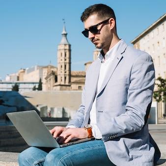 Homem de negócios moderno usando laptop ao ar livre