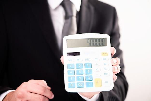 Homem de negócios mostrando figuras da calculadora de perto