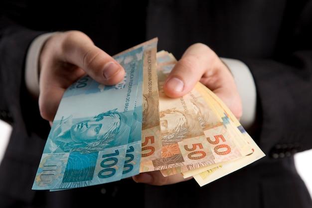 Homem de negócios, mostrando-lhe dinheiro brasileiro.