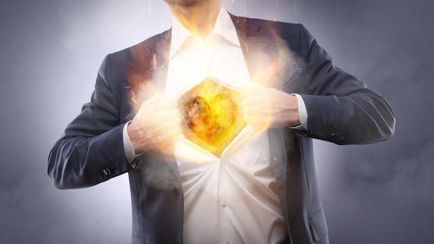 Homem de negócios mostrando um coração em chamas no peito em um terno - crm, conceito de negócio de mente de serviço