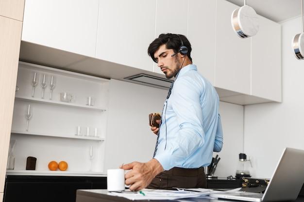 Homem de negócios na cozinha comer sanduíche usando o computador laptop com fones de ouvido, bebendo café.