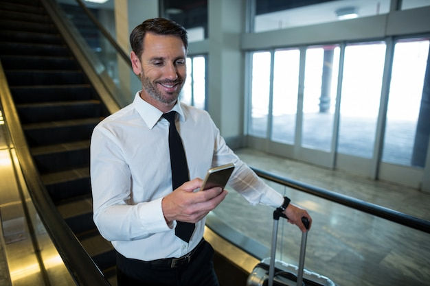 Homem de negócios na escada rolante usando telefone celular