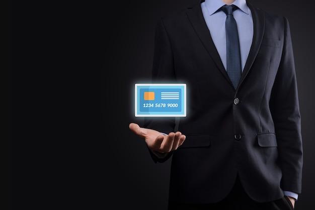 Homem de negócios na mão do terno segurando o ícone do cartão de crédito em branco mostrando para o conceito de serviços bancários e financeiros.