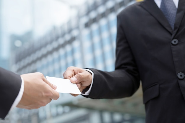 Homem de negócios na mão segurando show business cartões em branco cartão branco simulado arquivamento
