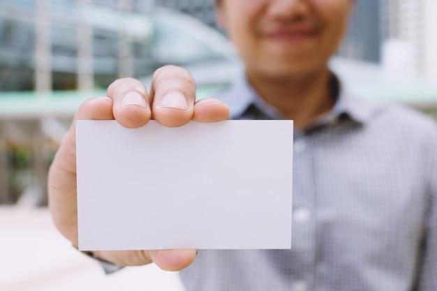 Homem de negócios na mão segure show cartão branco em branco simulado com cantos arredondados.