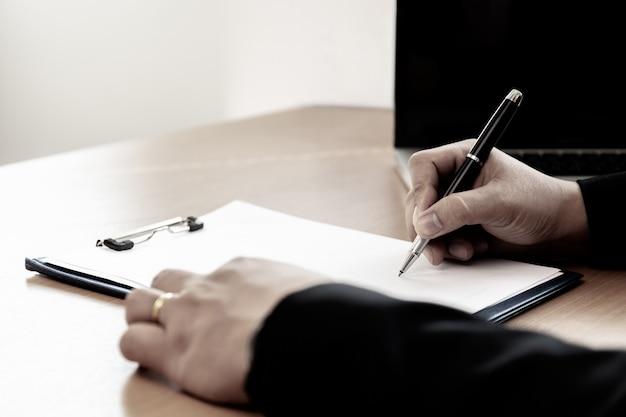 Homem de negócios na mesa de escritório que assina um formulário do contrato no escritório.