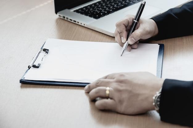 Homem de negócios na mesa de escritório que assina um formulário do contrato.
