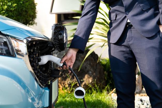 Homem de negócios na suíte enquanto carregava o carro elétrico.