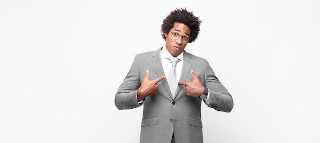 Homem de negócios negro afro apontando para si mesmo com um olhar confuso e curioso, chocado e surpreso ao ser escolhido