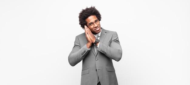 Homem de negócios negro afro se sentindo apaixonado e parecendo fofo, adorável e feliz, sorrindo romanticamente com as mãos ao lado do rosto