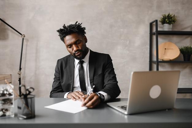 Homem de negócios negro focado em terno, fazendo videochamada com clientes no laptop