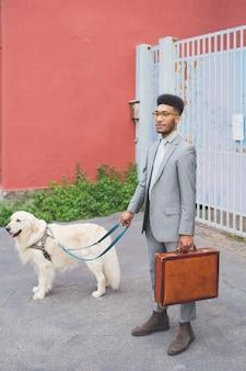Homem de negócios negro jovem caminhando para o trabalho ao ar livre com o cão na coleira