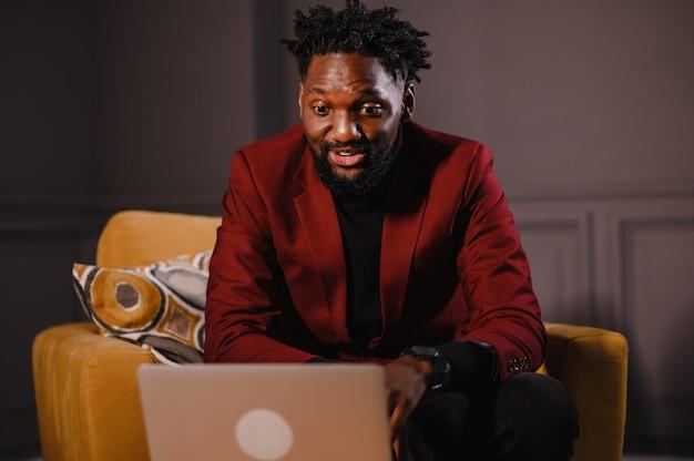 Homem de negócios negro trabalhando em um laptop e fazendo anotações