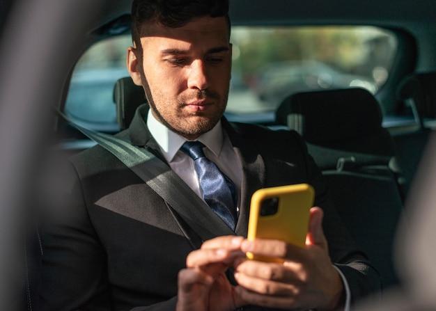 Homem de negócios no carro sendo o passageiro