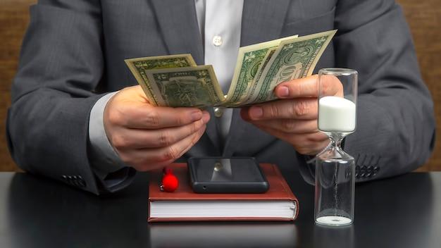 Homem de negócios no escritório conta dinheiro em um dos relógios de sol