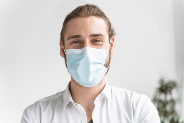 Homem de negócios no escritório usando máscara