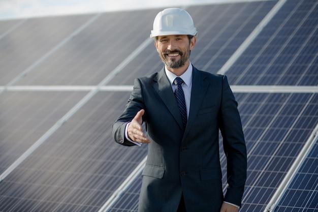 Homem de negócios no etation da energia solar que guarda a mão.