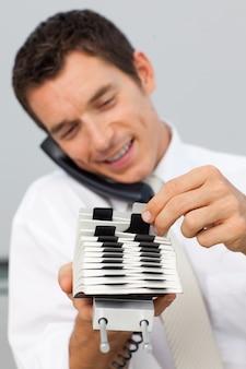 Homem de negócios no telefone e consultando um titular de cartão