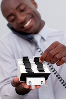 Homem de negócios no telefone e procurando por um detentor de índice