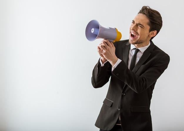 Homem de negócios no terno clássico que grita no altifalante.