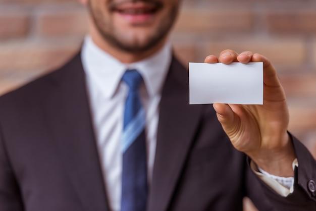 Homem de negócios no terno clássico que guarda um cartão branco.
