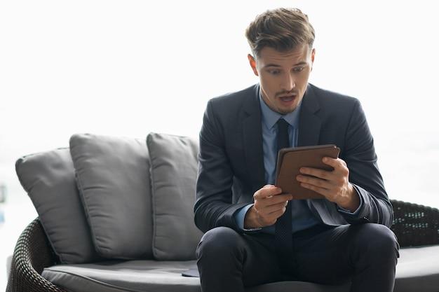 Homem de negócios novo choc que olha o tablet