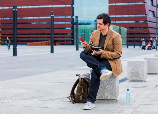 Homem de negócios novo com salada e telefone celular na cidade urbana exterior.