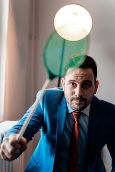 Homem de negócios novo considerável com swatter de mosca. olhando para a câmera.
