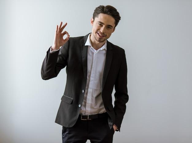 Homem de negócios novo considerável no sorriso clássico do terno.