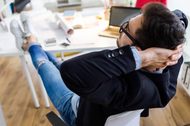 Homem de negócios novo considerável que relaxa um momento no escritório.