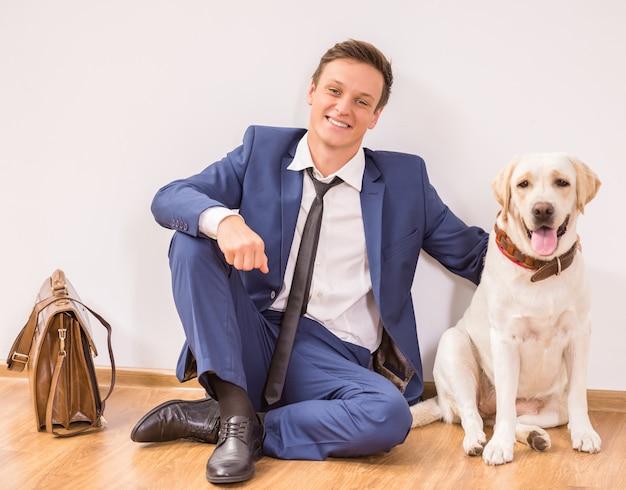 Homem de negócios novo de sorriso com seu cão que senta-se no assoalho.