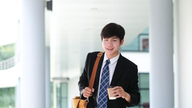 Homem de negócios novo de sorriso que guarda o copo de café quando a pausa para café.