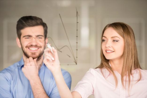 Homem de negócios novo e mulher de negócios que desenham um gráfico.