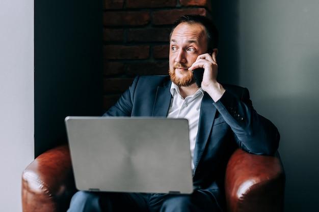 Homem de negócios novo em um terno que senta-se em uma cadeira com um portátil e que fala no telefone com a surpresa.
