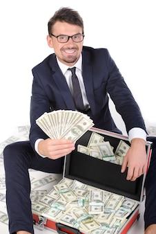 Homem de negócios novo feliz no formalwear que guarda o dinheiro.